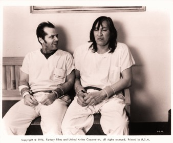 Jack Nicholson sitting on bench with Will Sampson in a scene from the film 'One Flew Over The Cuckoo's Nest', 1975. (Photo by United Artists/Getty Images)
