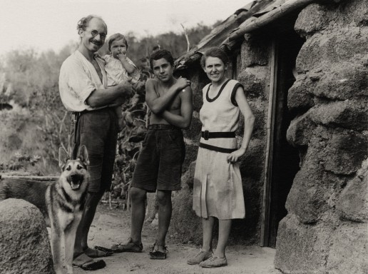 Heinz Wittmer holding baby Rolf and standing beside his son Harry and wife Margret with their dog Lump. In front of their first real house on Floreana Island